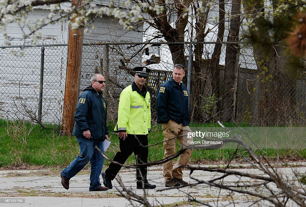 FBI investigators and watertown Police officer walk in parking lot near the boat where bombing suspect was hiding from police on Franklin Street on April 20, 2013 in Watertown, Massachusetts. A manhunt for Dzhokhar A. Tsarnaev, 19, a suspect in the Boston Marathon bombing ended after he was apprehended on a boat parked on a residential property in Watertown, Massachusetts. His brother Tamerlan Tsarnaev, 26, the other suspect, was shot and killed after a car chase and shootout with police. The bombing, on April 15 at the finish line of the marathon, killed three people and wounded at least 170
