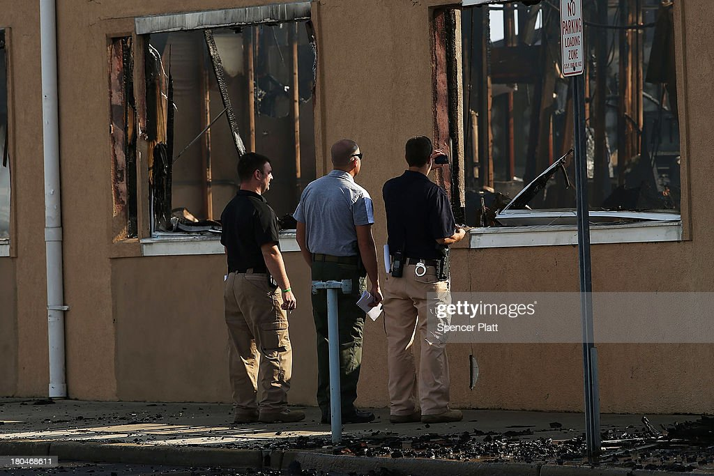 Investigators are viewed at the scene of a massive fire that destroyed dozens of businesses along an iconic Jersey shore boardwalk on September 13, 2013 in Seaside Heights, New Jersey. The 6-alarm fire began in a frozen custard stand on the recently rebuilt boardwalk around 2:00 p.m. on Thursday, September 12, and quickly spread in high winds. While there were no injuries reported, many businesses that had only recently re-opened after Hurricane Sandy were destroyed in the blaze.