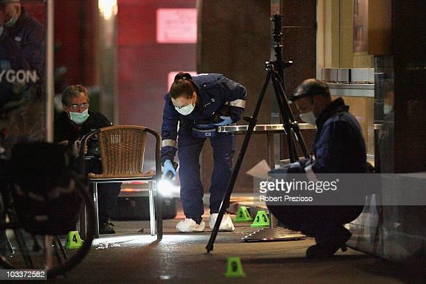 Investigators asses the crime scene where two men were shot dead on Lygon Street in the CBD on August 13 2010 in Melbourne Australia The two men said...