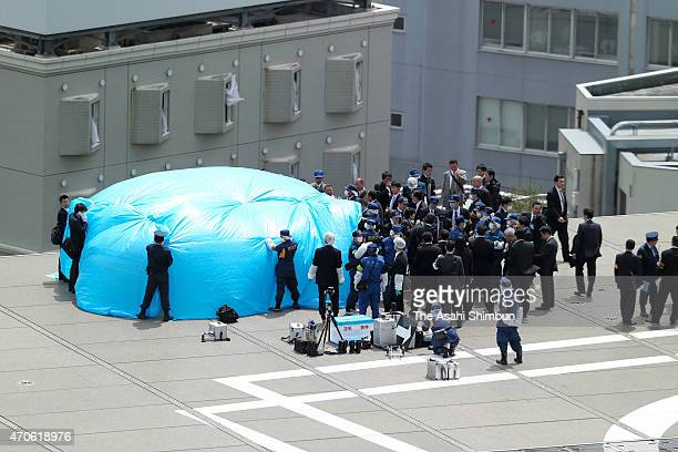 Investigators check a drone under tarpaulin on the roof of the prime minister's official residence on April 22 2015 in Tokyo Japan A small...