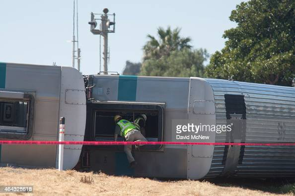 Investigators climb into the wreckage of a Los Angelesbound Metrolink train that derailed in a fiery collision with a truck on the tracks on February...