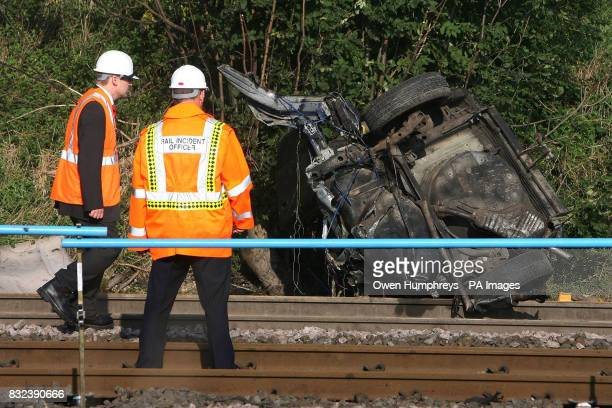 Investigators examine part of the car which collided with a train killing the motorist late Monday evening on the East Coast Main Line in the village...