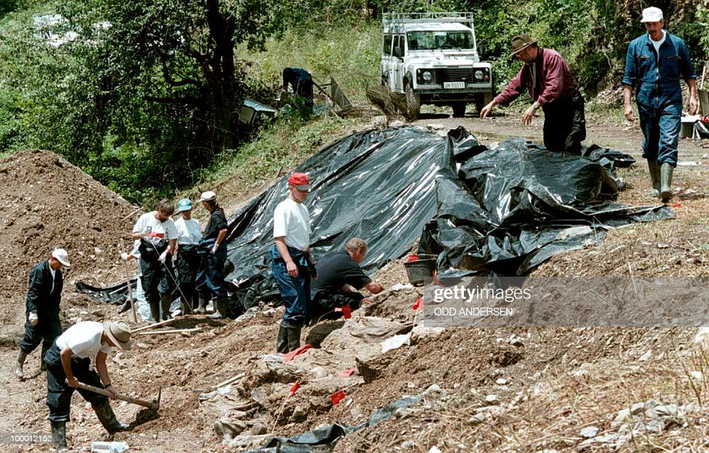 Investigators from ICTY (International Criminal Tribunal for the former Yugoslavia) cover up exposed bodies to protect the remains from the weather near the village of Cerska some 65 km southeast of Tuzla in the Serb entity, 11 July 1996. The investigators continued to excavate this mass grave near a dirt road for the fifth day in a row.