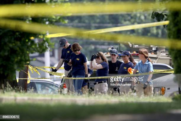 Investigators from the FBI look for evidence in a parking next to Eugene Simpson Field the site where a gunman opened fire June 14 2017 in Alexandria...