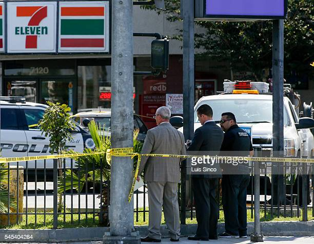 Investigators from the Los Angeles County Sheriff Department stand in front of the 7Eleven store at the corner of Florence and Atlantic Avenues in...