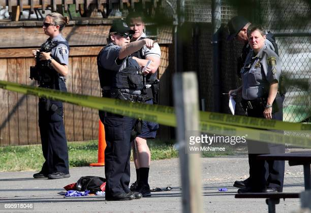 Investigators gather at Eugene Simpson Field the site where a gunman opened fire June 14 2017 in Alexandria Virginia Multiple injuries were reported...