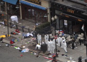 Investigators in white jumpsuits work the crime scene on Boylston Street following yesterday's bomb attack at the Boston Marathon April 16 2013 in...
