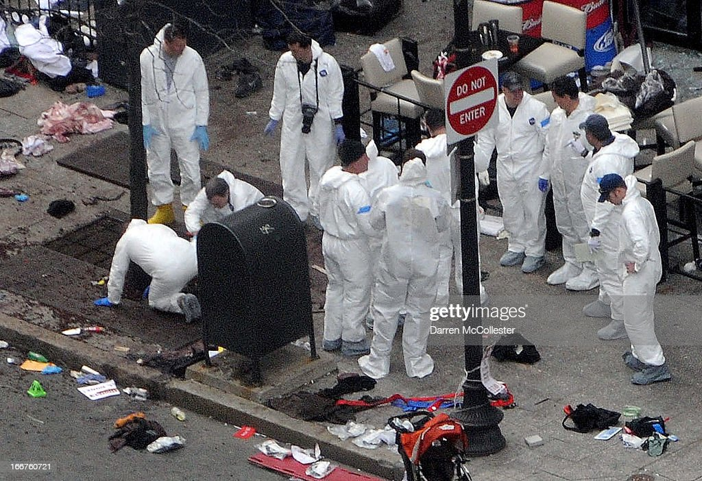 Investigators in white jumpsuits work the crime scene on Boylston Street following yesterday's bomb attack at the Boston Marathon April 16, 2013 in Boston, Massachusetts. Security is tight in the City of Boston following yesterday's two bomb explosions near the finish line of the Boston Marathon, that killed three people and wounding hundreds more.