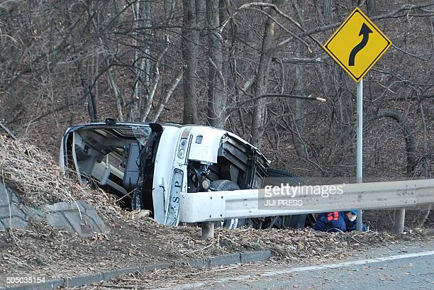 Investigators inspect the wreckage of a bus which crashed after running off a road in Karuizawa Nagano prefecture on January 15 2016 Fourteen people...