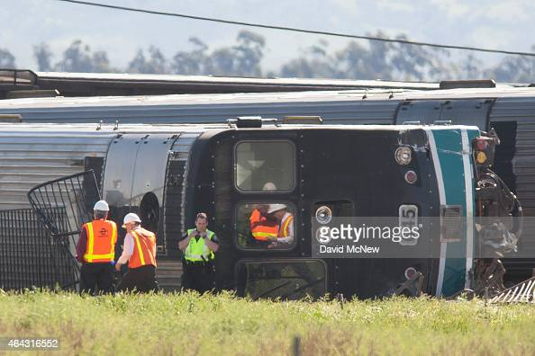 Investigators look at overturned rail cars at the site where a Los Angelesbound Metrolink train derailed in a fiery collision with a truck on the...