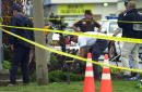 Investigators look for evidence across from an Exxon gas station on Route 1 October 11 2002 in Fredericksburg Virginia Police throughout the...