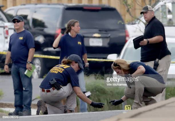 Investigators look for evidence in a parking next to Eugene Simpson Field the site where a gunman opened fire June 14 2017 in Alexandria Virginia...