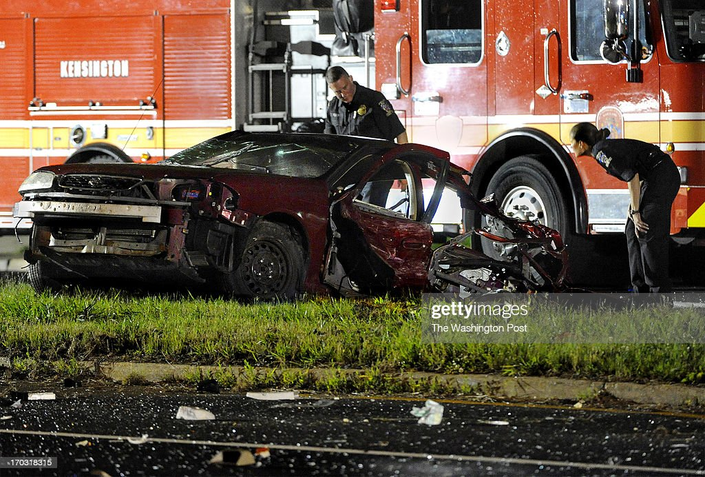 Investigators look over the front end of a car that was torn in half after it ended up in the median on Georgia Ave. following a fatal 3-vehicle crash that killed a total of 3 people. The Montgomery County police say the crash happened at 9:47 p.m. Sunday at Georgia Avenue and Kayson Street. Police said the adult and child were pronounced dead at the scene. Four other adults were taken to hospitals, including one who died later. Photo by Michael S. Williamson/The Washington Post via Getty Images