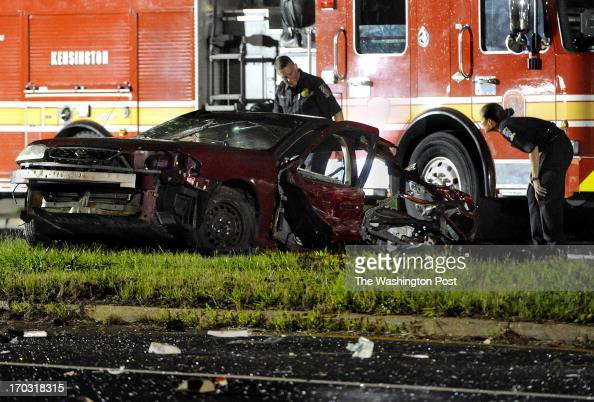 Investigators look over the front end of a car that was torn in half after it ended up in the median on Georgia Ave following a fatal 3vehicle crash...