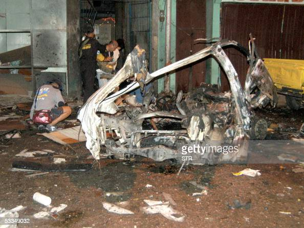 Investigators look through the wreckage of a van in the southern Philippine city of Zamboanga after a bomb went off inside the vehicle 10 August 2005...