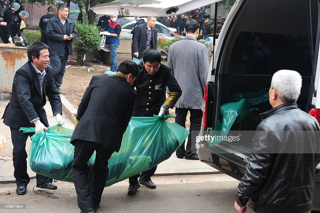 Investigators move a victim's body into a van as they work at the scene where attackers armed with knives killed three people in Changsha, central China's Hunan province on March 14, 2014. Attackers armed with knives killed three people in China on March 14, an official said, ruling out terrorism two weeks after a mass stabbing blamed on Xinjiang militants left 29 people dead and stunned the nation. CHINA