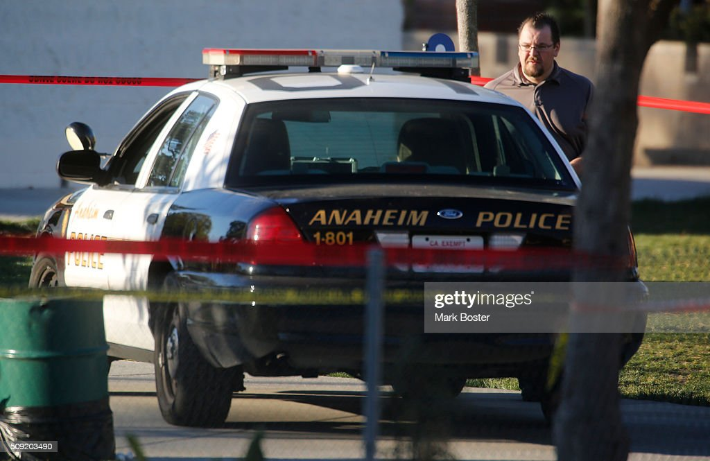Investigators pass by the patrol car where an Anaheim Police Officer fatally wounded a 22-year-old man in Sage Park in Anaheim February 9, 2016. Officers were originally called to a nearby apartment complex where a man was knocking on doors. Police apparently confronted a man in the park and an officer involved shooting occurred.