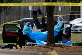Investigators remove a body as they work a crime scene outside the Curtis Culwell Center after a shooting occurred the day before May 04 2015 in...