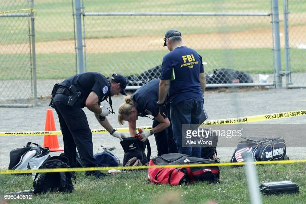 Investigators search the bags that have been left behind at the Eugene Simpson Stadium Park where a shooting had happened June 14 2017 in Alexandria...