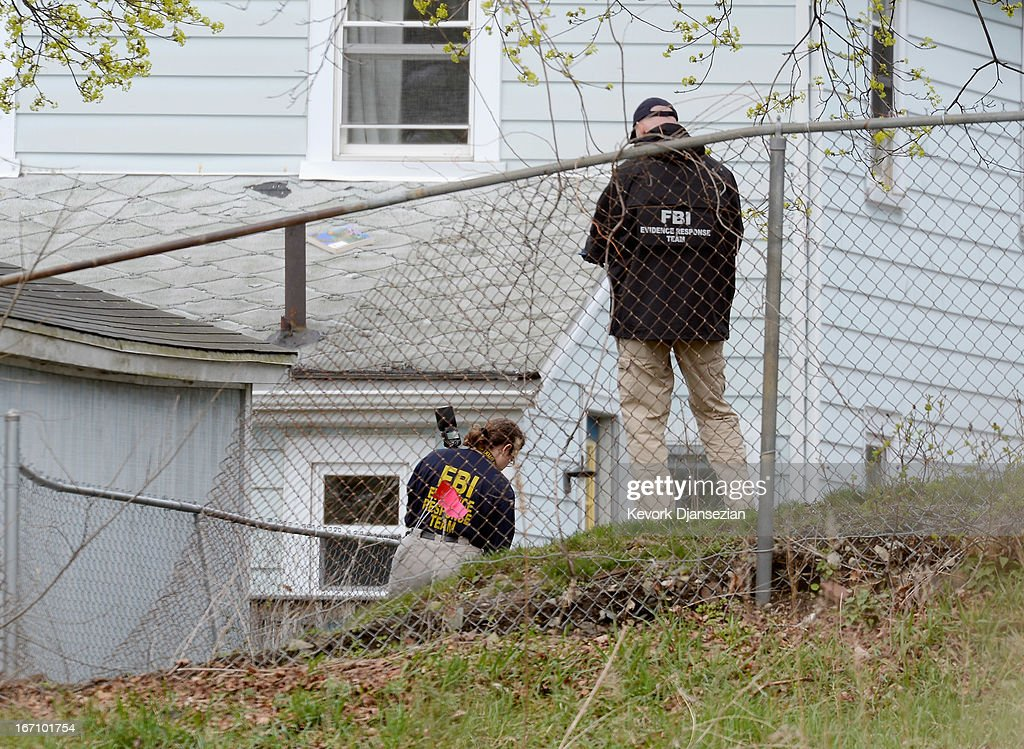 FBI investigators search the shooting scene near the boat where bombing suspect was hiding from police on Franklin Street on April 20, 2013 in Watertown, Massachusetts. A manhunt for Dzhokhar A. Tsarnaev, 19, a suspect in the Boston Marathon bombing ended after he was apprehended on a boat parked on a residential property in Watertown, Massachusetts. His brother Tamerlan Tsarnaev, 26, the other suspect, was shot and killed after a car chase and shootout with police. The bombing, on April 15 at the finish line of the marathon, killed three people and wounded at least 170