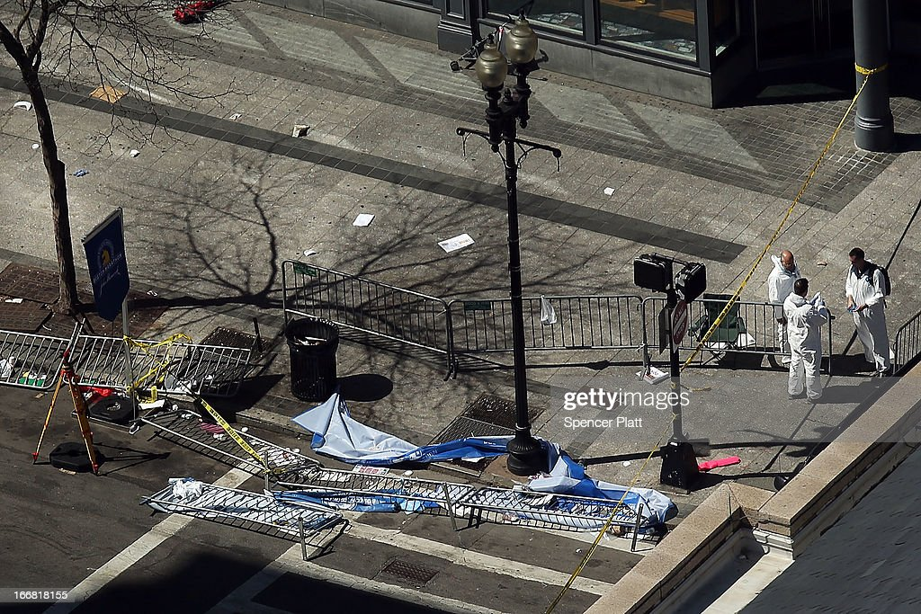 Investigators stand at the scene of twin bombings at the Boston Marathon on April 17, 2013 in Boston, Massachusetts. The explosions, which occurred near the finish line of the 116-year-old Boston race on April 15, resulted in the deaths of three people with more than 170 others injured. Security has been heightened across the nation as the search continues for the person or people behind the bombings.