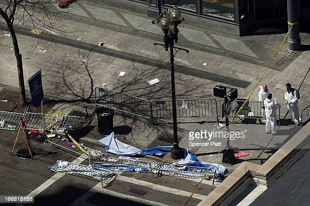 Investigators stand at the scene of twin bombings at the Boston Marathon on April 17 2013 in Boston Massachusetts The explosions which occurred near...