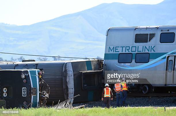 Investigators stand beside overturned rail cars following a collision with a truck that was hit by a Los Angelesbound Metrolink train in Oxnard...
