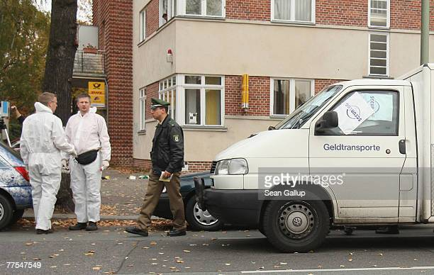 Investigators stand next to an armoured money transporter outside a branch of Postbank bank after an attempted robbery that left one guard dead...