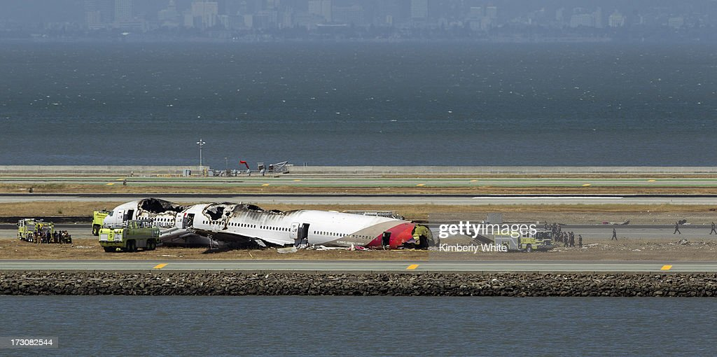 Investigators surround the remains of a Boeing 777 airplane on the tarmac after it crashed while landing at San Francisco International Airport July 6, 2013 in San Francisco, California. An Asiana Airlines passenger aircraft coming from Seoul, South Korea crashed while landing. There has been no official confirmation of casualties.