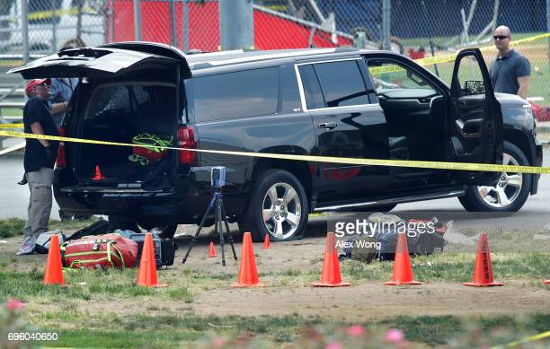 Investigators survey a black SUV with a flat tire and a hole on its windshield outside the Eugene Simpson Stadium Park where a shooting had happened...