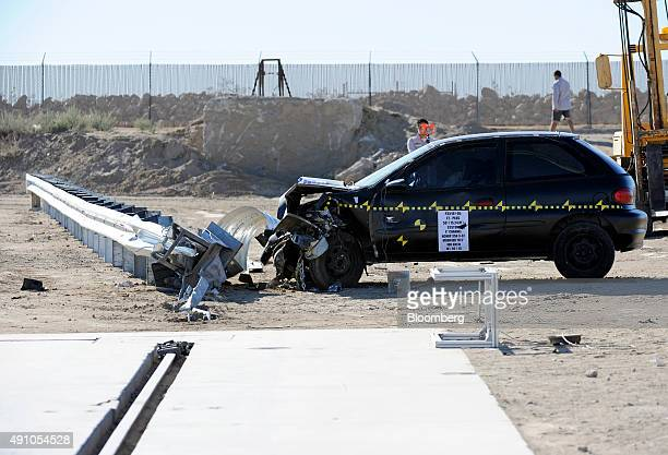 Investigators survey the damage on a compact coupe after a crash test at Karco Engineering LLC safety testing facility in Adelanto California US on...