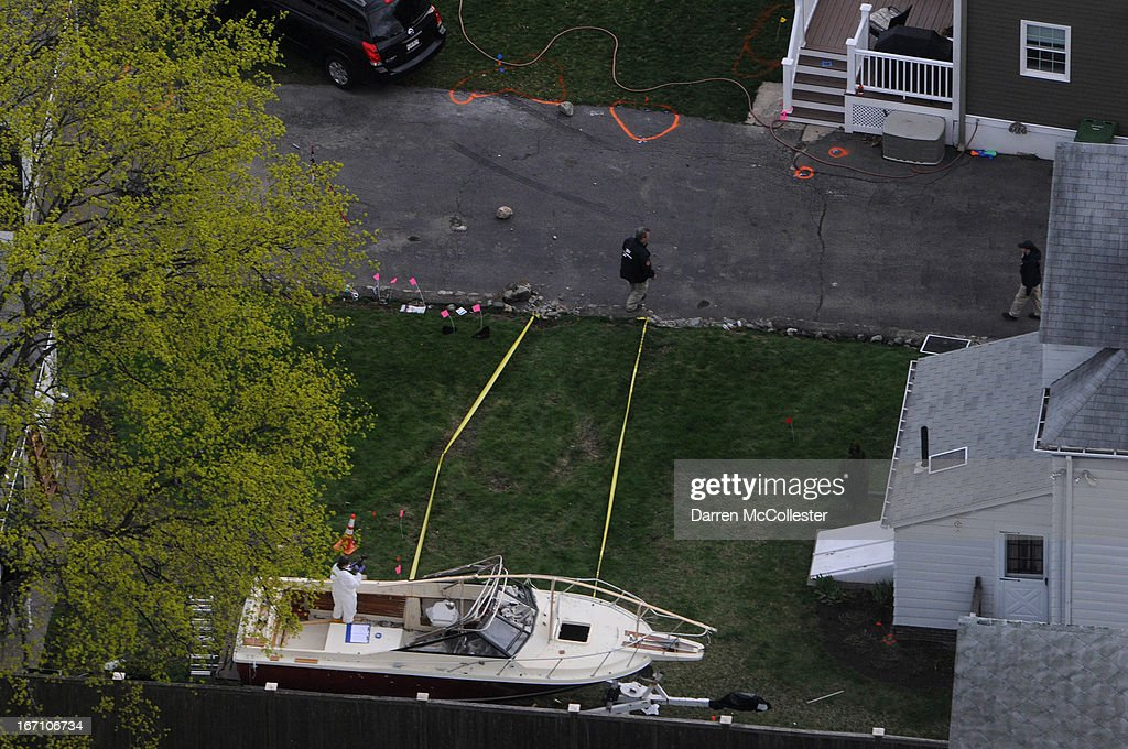 Investigators work around the boat where Dzhokhar A Tsarnaev was found hiding after a massive manhunt in the backyard of a Franklin Street home in an...