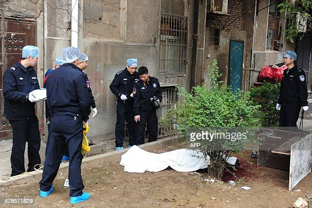 Investigators work at the crime scene near a victim's body where attackers armed with knives killed three people in Changsha central China's Hunan...