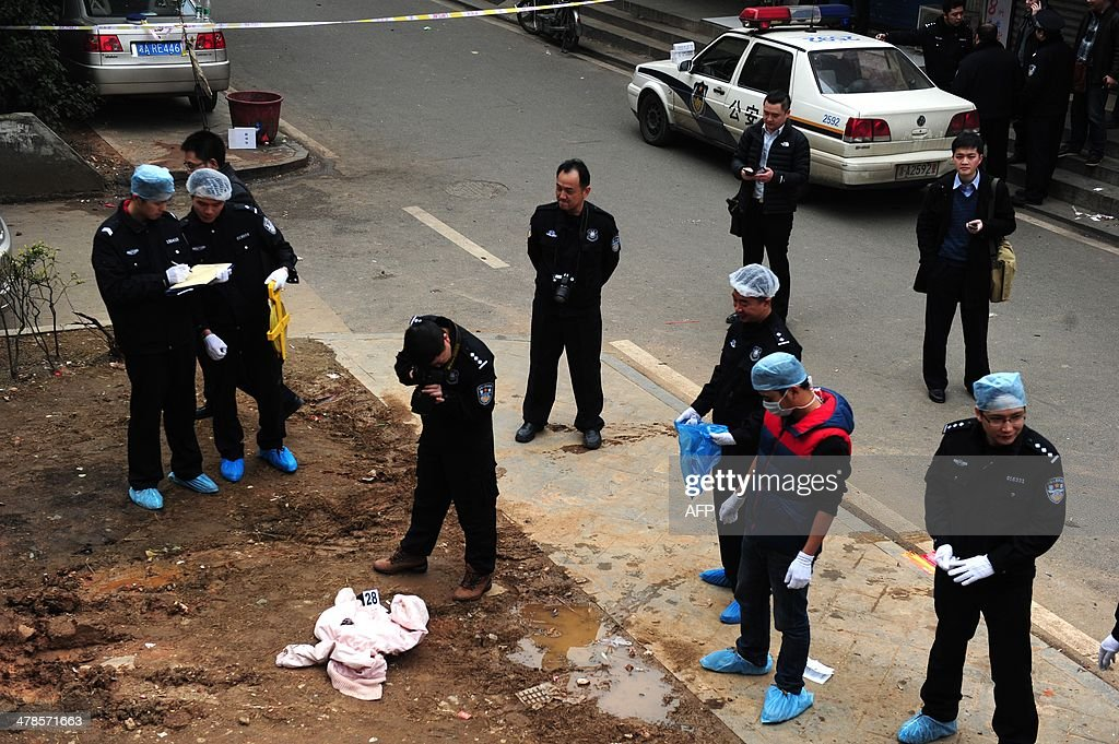 Investigators work at the scene where attackers armed with knives killed three people in Changsha, central China's Hunan province on March 14, 2014. Attackers armed with knives killed three people in China on March 14, an official said, ruling out terrorism two weeks after a mass stabbing blamed on Xinjiang militants left 29 people dead and stunned the nation. CHINA