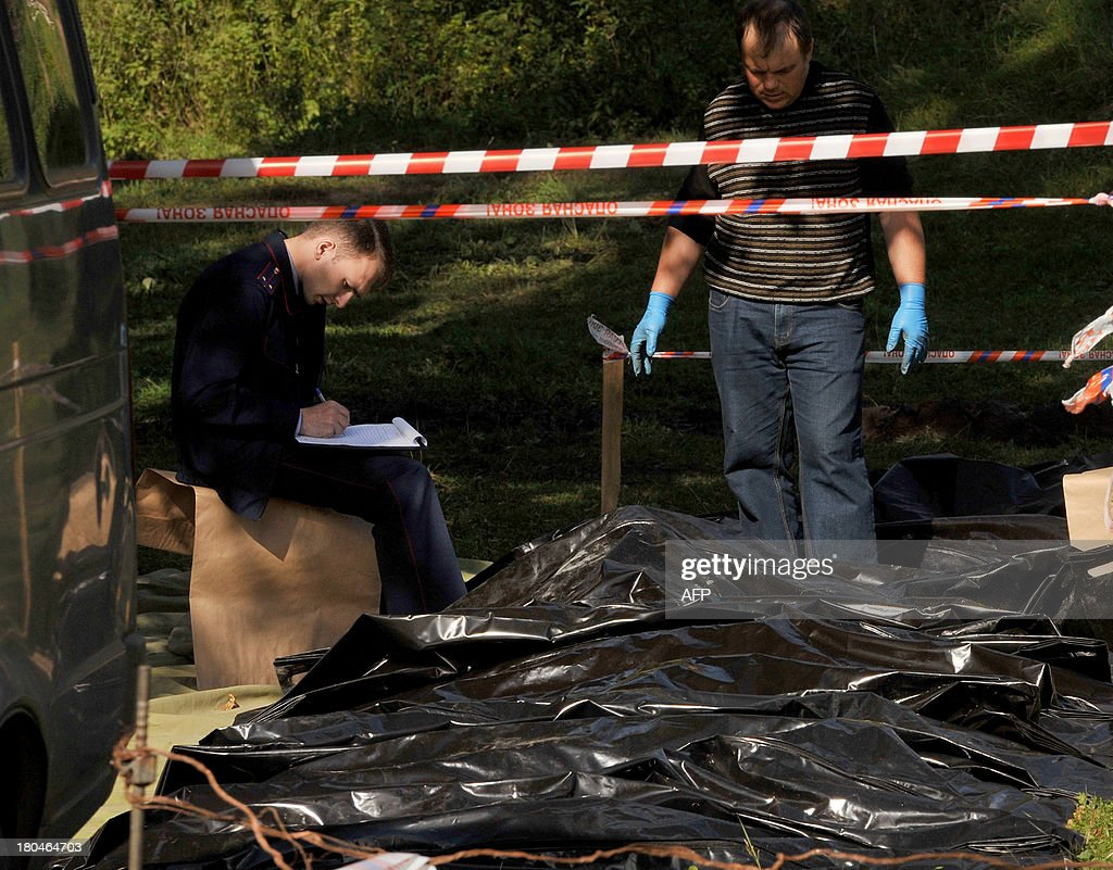 Investigators work near body bags with victims of a pre-dawn fire in a psychiatric hospital in the village of Luka in the northwest Russian Novgorod region, 220 kilometres (137 miles) southeast of Saint Petersburg, on September 13, 2013. Thirty seven people were killed when a fire swept through a wooden psychiatric hospital in northwest Russia overnight yesterday, regional investigators said.