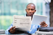Investor compares quotes from newspaper and tablet