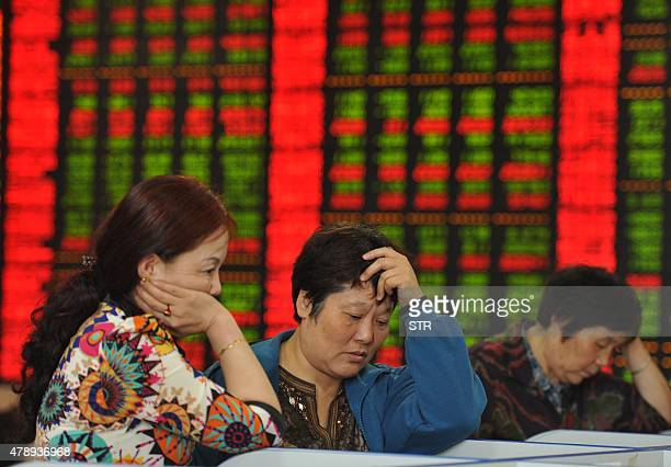 Investors check share prices in a stock firm in Fuyang east China's Anhui province on June 29 2015 Chinese shares plunged in morning trading on June...