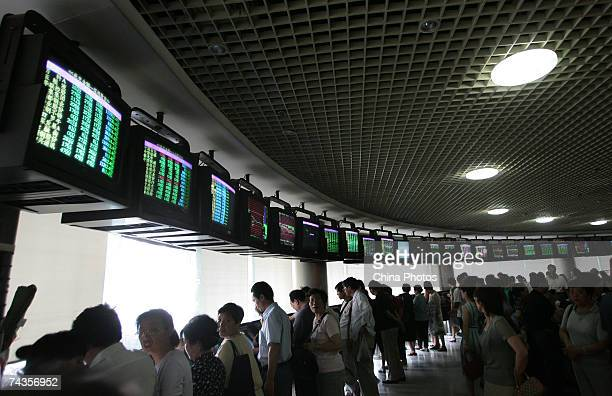 Investors gather to view the stock index at a securities company on May 30 2007 in Nanjing China The Shanghai Composite Index fell by 65% today after...
