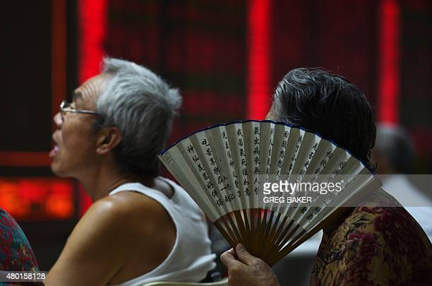 Investors look at a board showing stock market movements at a securities company in Beijing on July 10 2015 Chinese stocks surged for a second day on...