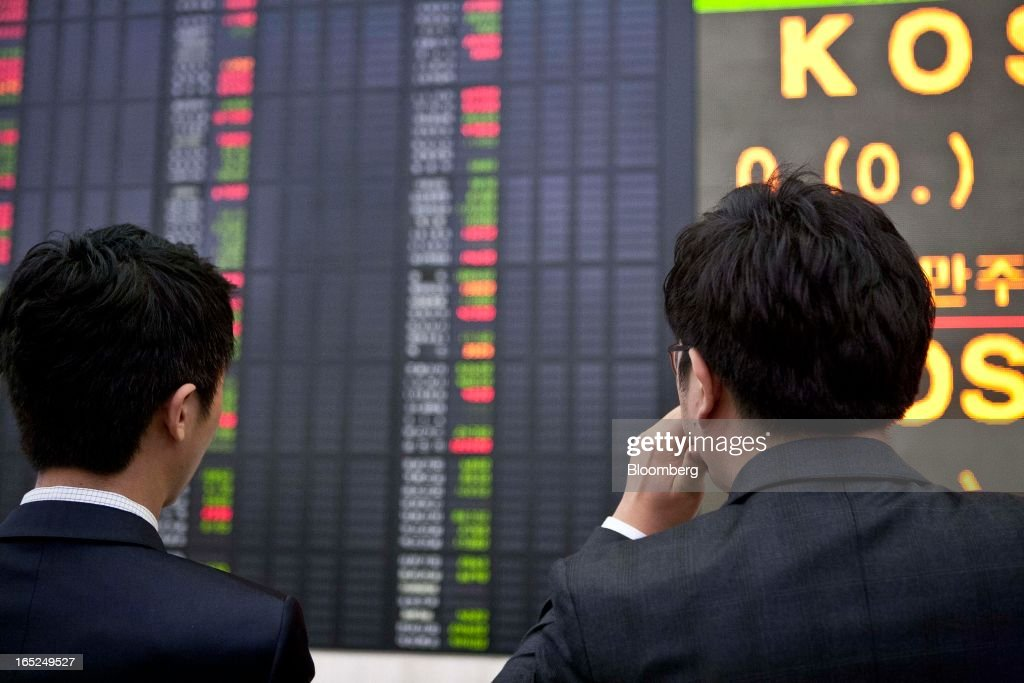 Investors look at a stock board at a Daishin Securities Co. branch in Seoul, South Korea, on Tuesday, April 2, 2013. International investors sold the most South Korean equities in 10 months in March amid concerns the nation's exporters will lose market share to Japanese rivals and as tension with North Korea rose. Photographer: Jean Chung/Bloomberg via Getty Images