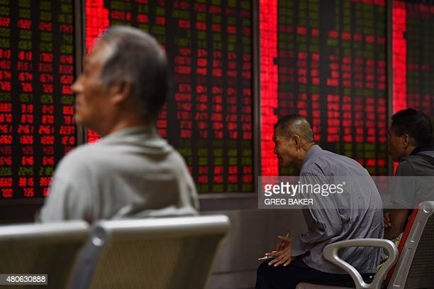 Investors look at screens showing stock market movements at a securities company in Beijing on July 14 2015 Hundreds of firms were expected to resume...