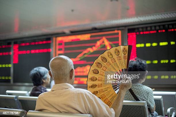 Investors look at screens showing stock market movements at a securities company in Beijing on July 28 2015 Chinese shares sank on July 28 a day...