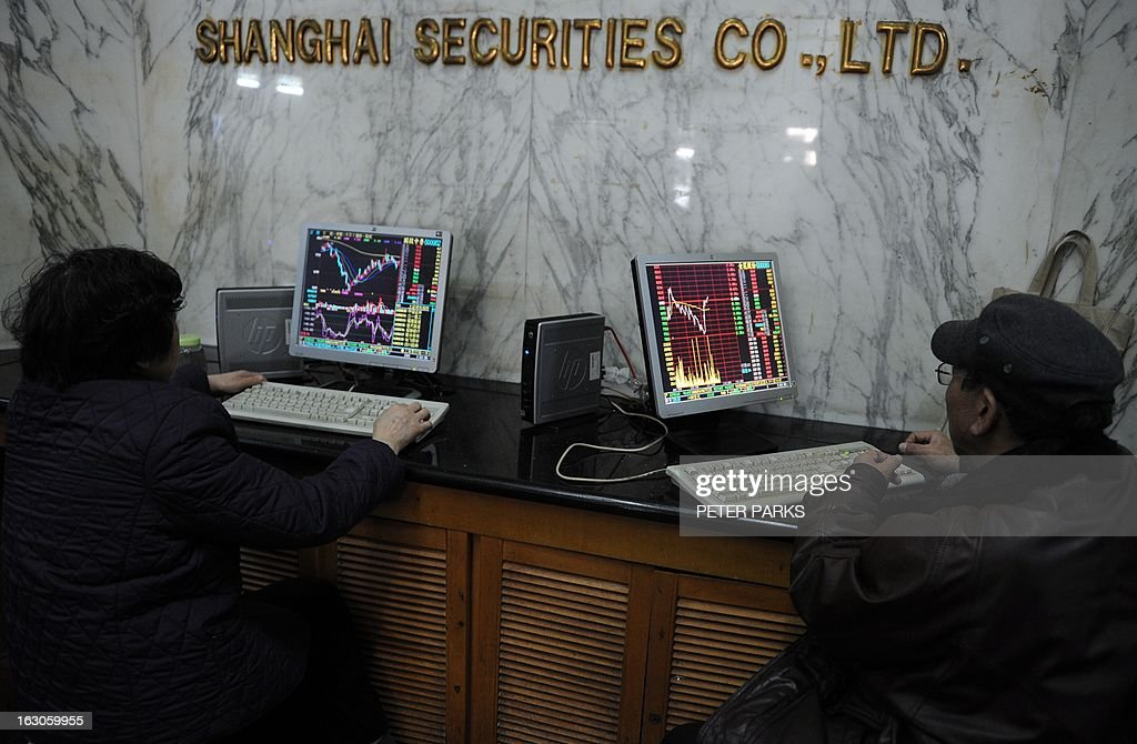 Investors look at stock prices on a screen at a securities exchange in Shanghai on March 4, 2013. Chinese shares were down 3.05 percent in early afternoon trade as property stocks were hit by government measures announced last week to control housing prices, dealers said. AFP PHOTO/Peter PARKS