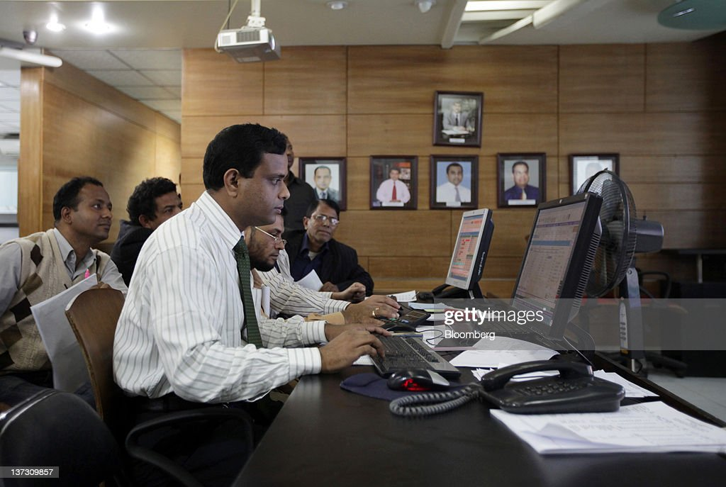 Investors monitor financial information on computers at the Dhaka Stock Exchange in Dhaka, Bangladesh, on Sunday, Jan. 8, 2012. Bangladesh's central bank this month raised interest rates for the second time in four months to curb inflation that has exceeded 9 percent since the start of 2011. Photographer: Tomohiro Ohsumi/Bloomberg via Getty Images