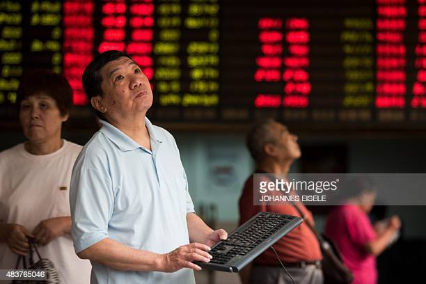 Investors monitor screens showing stock market movements at a brokerage house in Shanghai on August 13 2015 Shanghai shares were down 062 percent...
