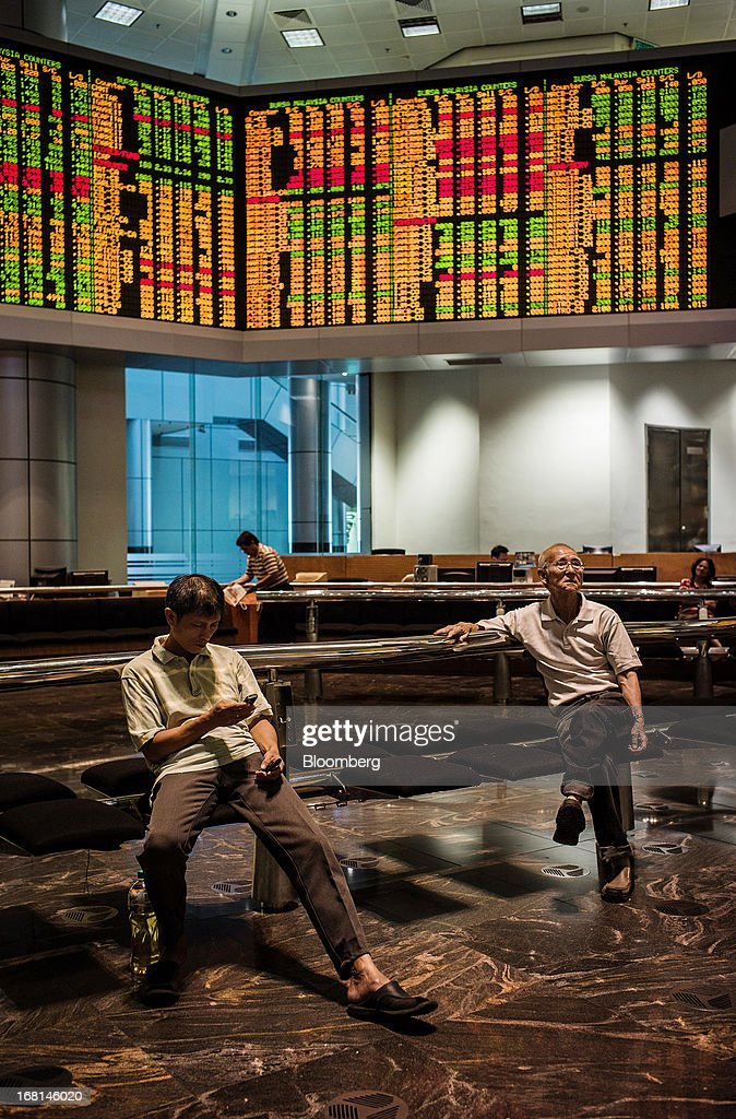 Investors monitor stock prices in the trading gallery at the RHB Investment Bank Bhd. headquarters in Kuala Lumpur, Malaysia, on Monday, May 6, 2013. The biggest surge in Malaysian stocks since 2008 has turned into a money-losing day for investors who piled in at the height of the rally sparked by Prime Minister Najib Razak's election victory. Photographer: Sanjit Das/Bloomberg via Getty Images