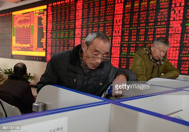 Investors observe stock market at an exchange hall on December 17 2015 in Fuyang Anhui Province of China The Shanghai Composite Index rose 6381...
