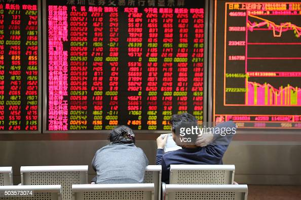 Investors observe stock market at an exchange hall on January 6 2016 in Beijing China Chinese stock market rebounded after two days' decline The...