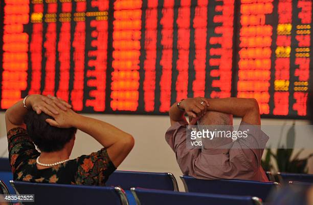 Investors observe stock market data at a stock exchange hall on August 10 2015 in Fuyang Anhui Province of China Chinese shares rebounded on Monday...