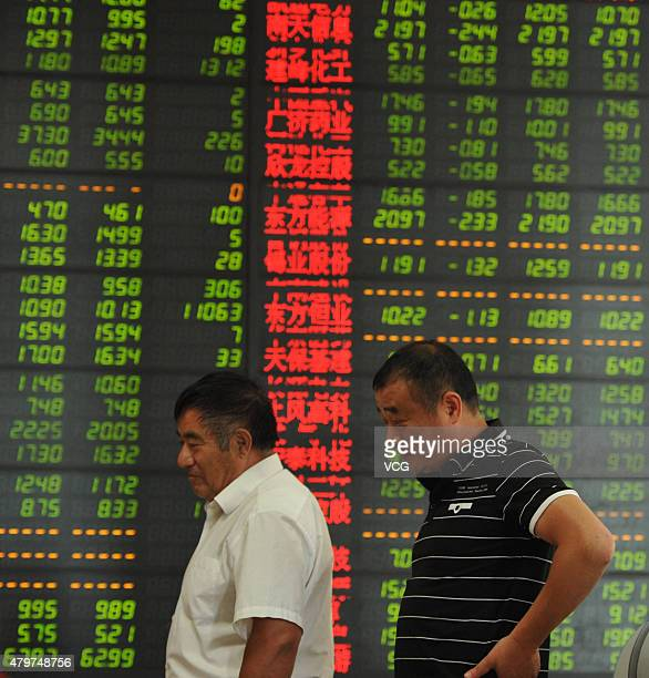 Investors observe the stock market at a stock exchange hall on July 7 2015 in Fuyang Anhui Province of China Chinese shares rebounded to 3700 points...